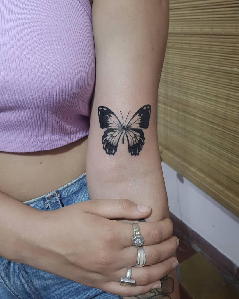 medium-sized black and grey tattoo on woman's upper arm of realistic butterfly