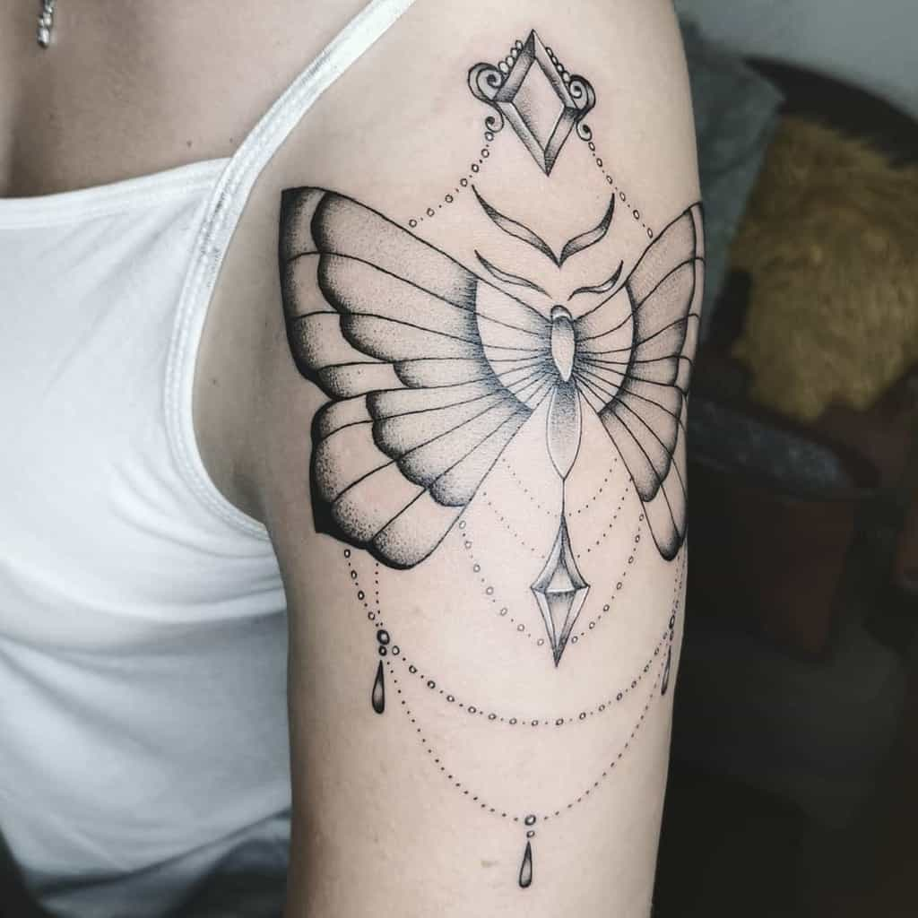 large black and grey tattoo on woman's upper arm of ornamental butterfly