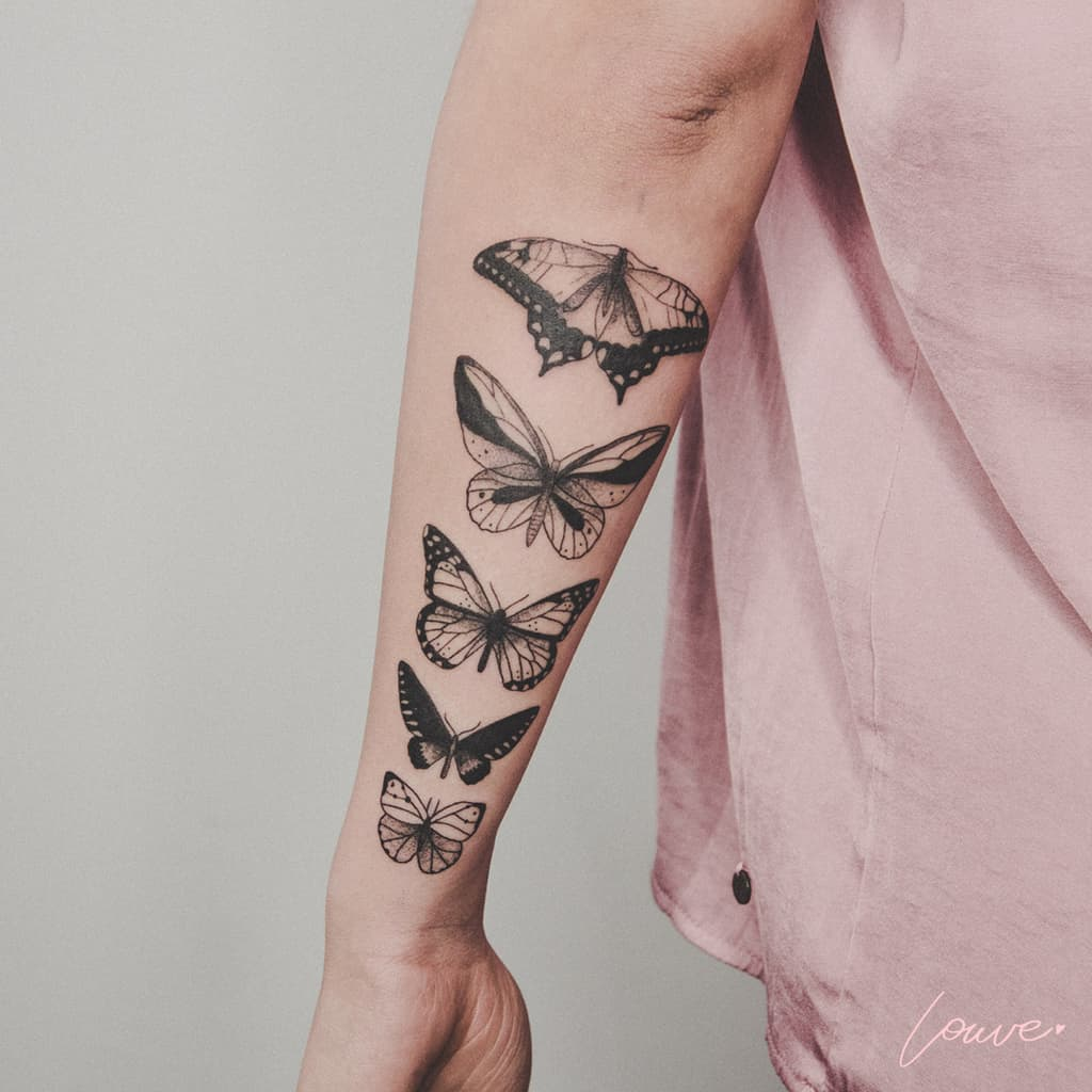 large black and grey detailed tattoos on forearm of five realistic butterflies in a row