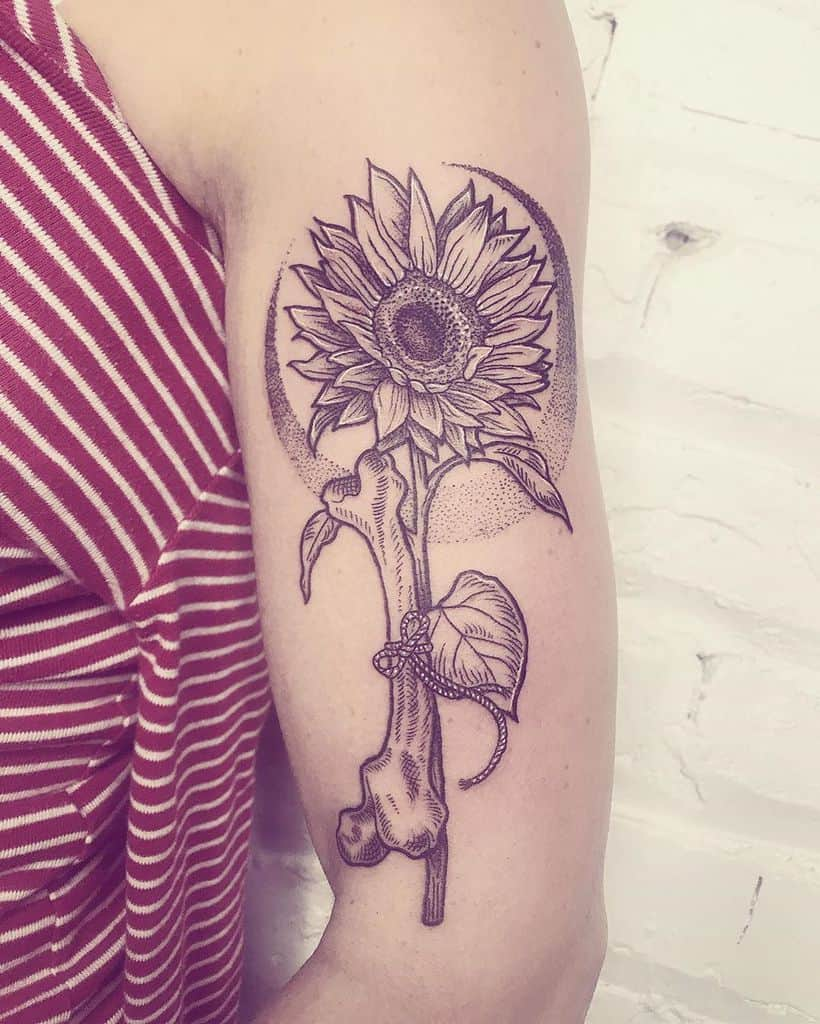 large black and grey dotwork tattoo on upper arm of realistic sunflower with bone tied to its stem and crescent moon behind