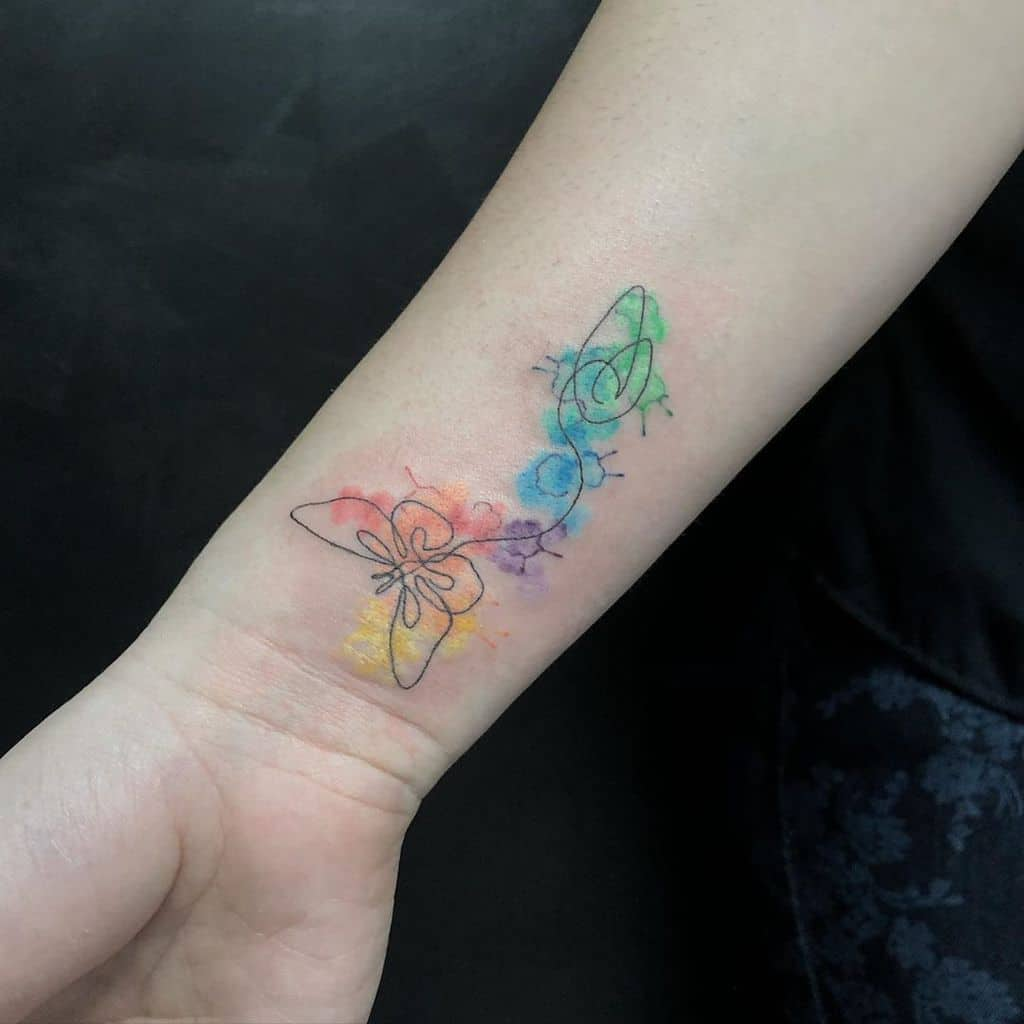 small color watercolor tattoo on woman's inner forearm of surrealistic line butterfly drawing