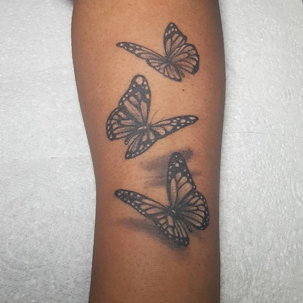 large black and grey tattoos on woman's lower leg of three realistic butterflies flying with shadow