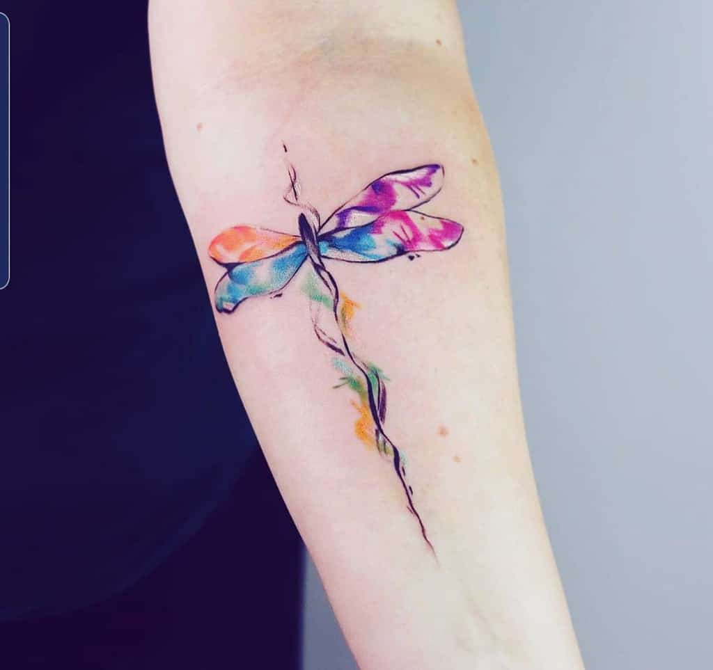The vivid and flamboyant dragonfly accentuating the arm raising a sense of enjoyment