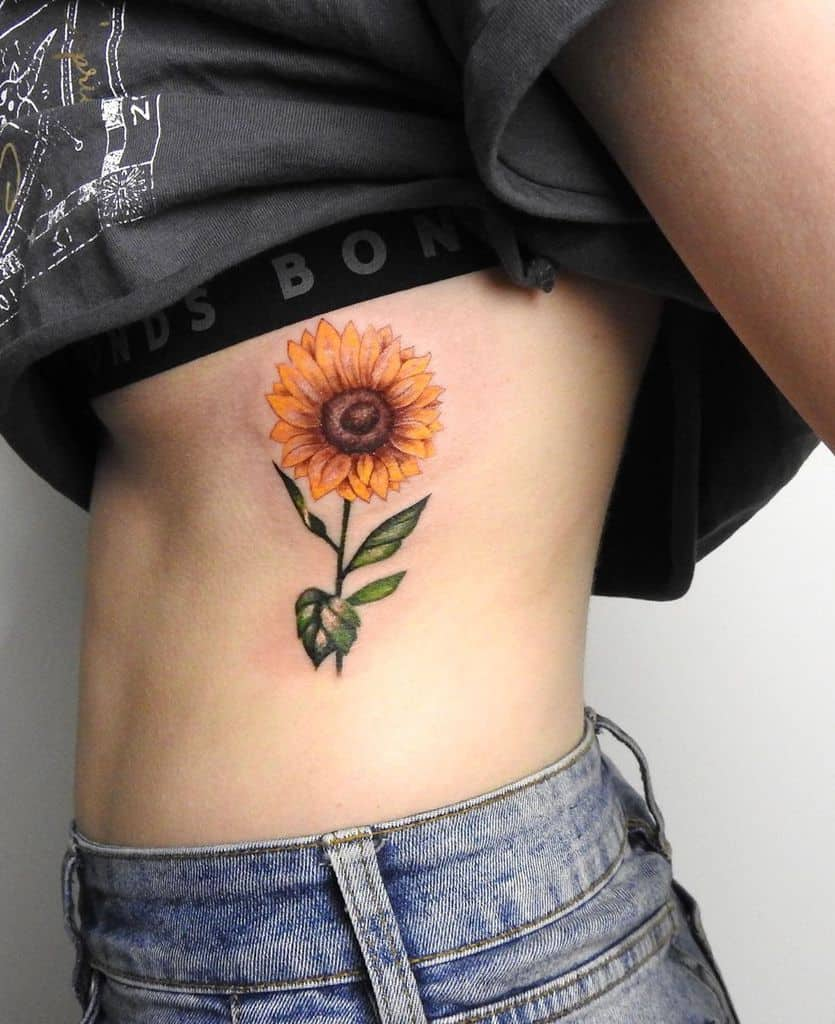 medium-sized color tattoo on woman's ribs of realistic sunflower with stem