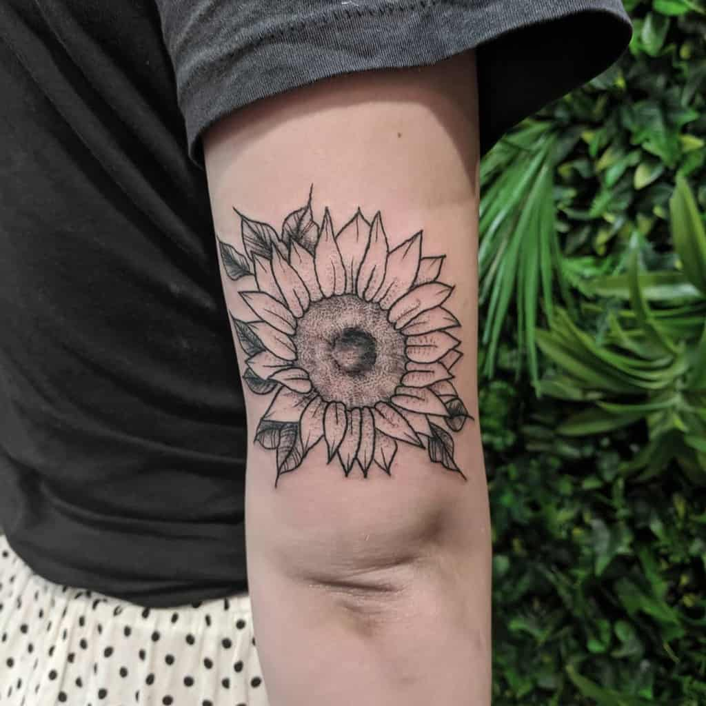 medium-sized black and grey tattoo of a sunflower on back of woman's upper arm