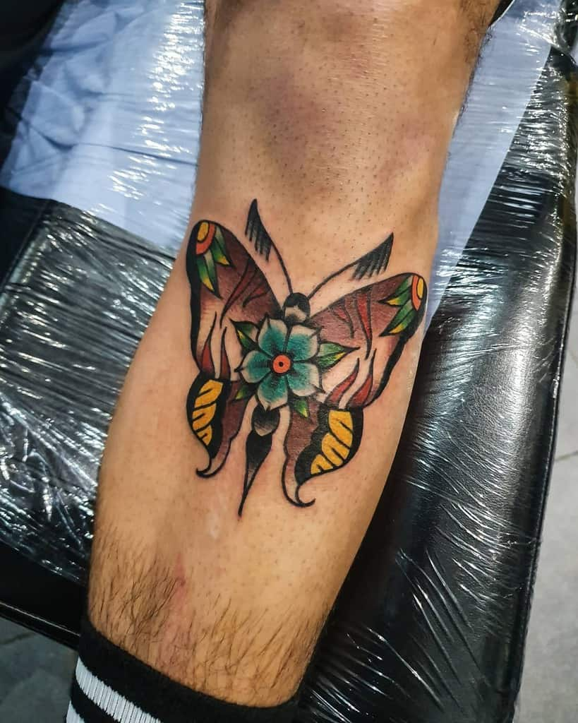 large color traditional tattoo on man's lower leg below knee of a surrealistic butterfly with hibiscus flower in its center