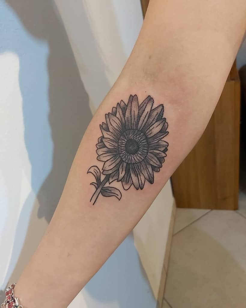 medium-sized black and grey tattoo on woman's forearm of a sunflower