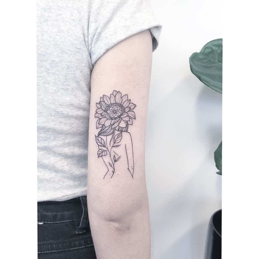 medium-sized black and grey line tattoo on back of woman's upper arm of a woman with a sunflower over her head