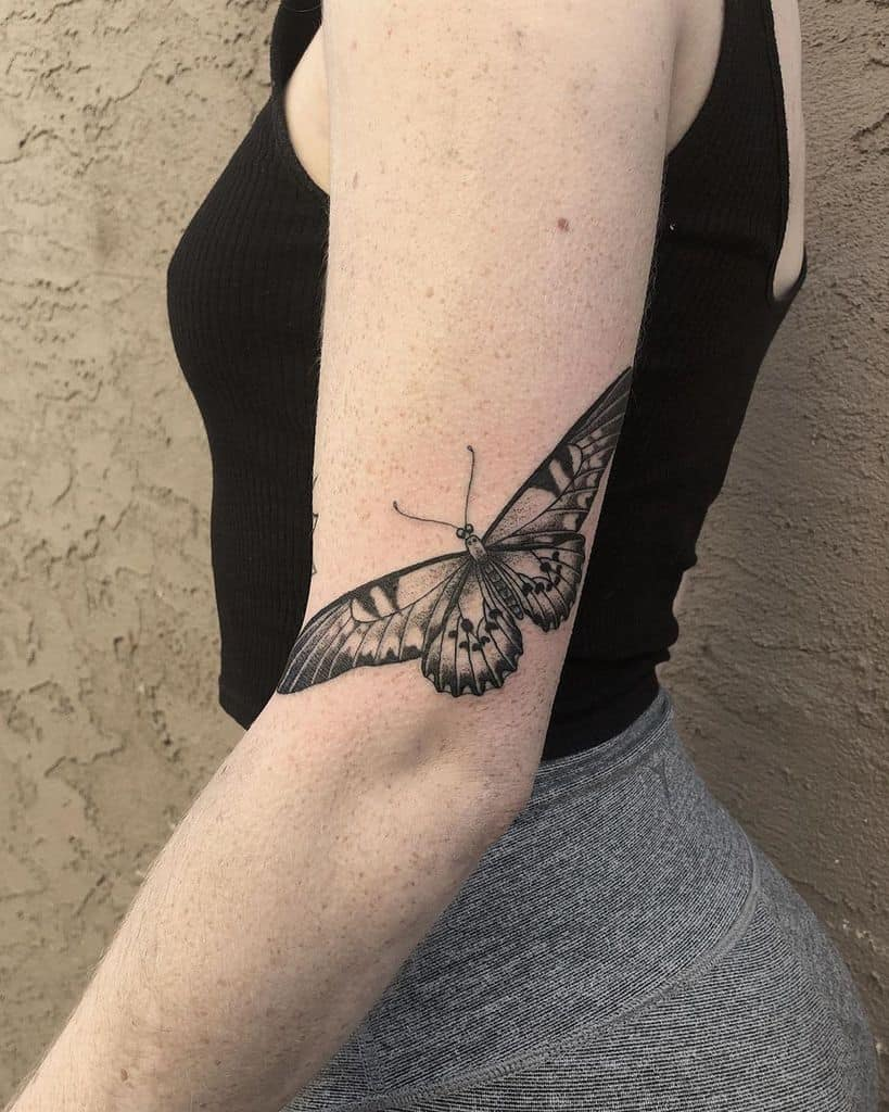 medium-sized black and grey tattoo on back of woman's upper arm of realistic butterfly