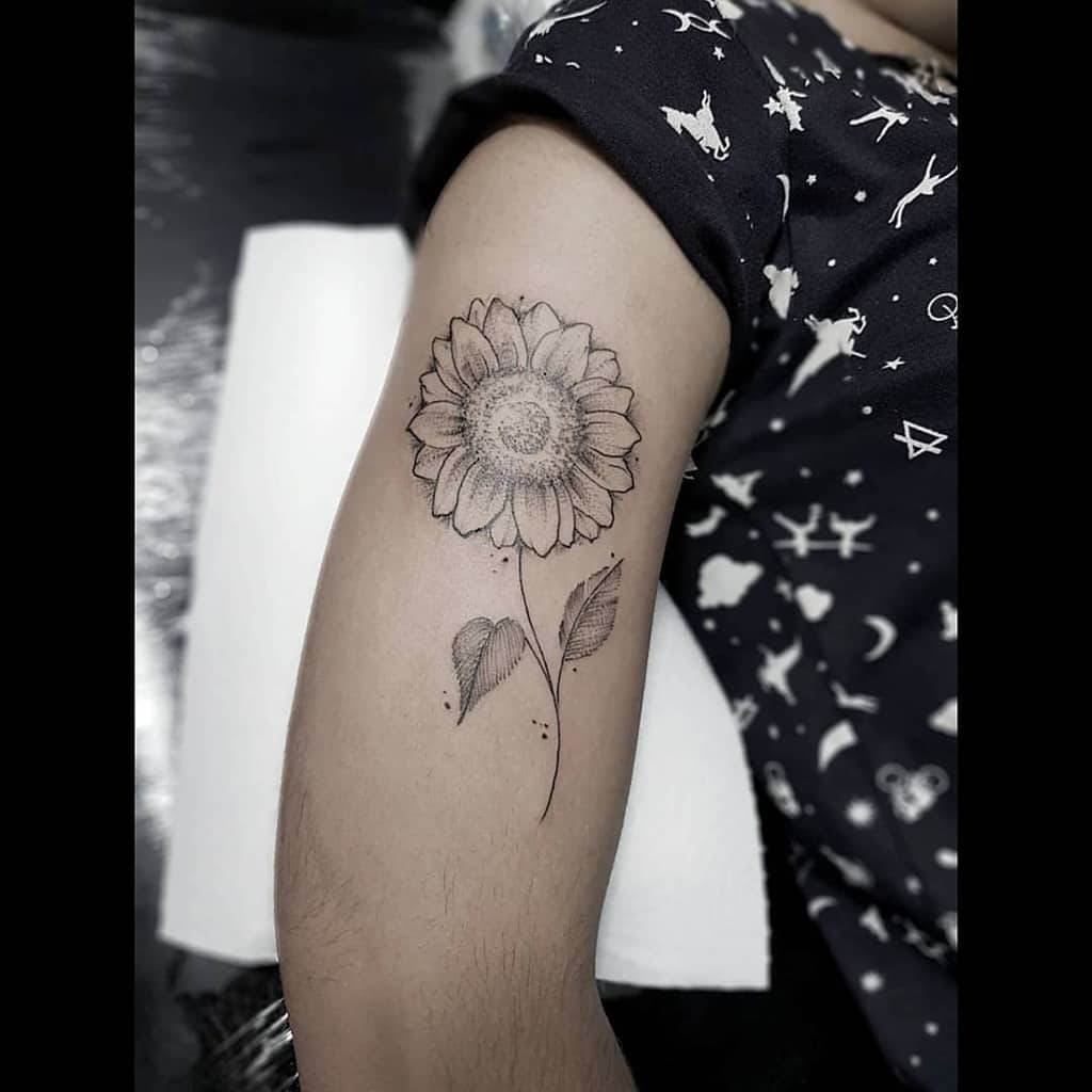 large black and grey surrealism tattoo on woman's upper arm of a sunflower with stem
