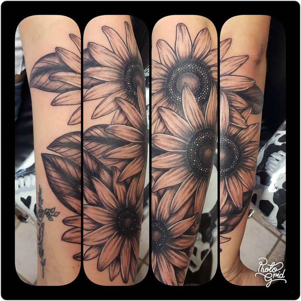 large black and grey tattoo on woman's forearm of three realistic sunflowers