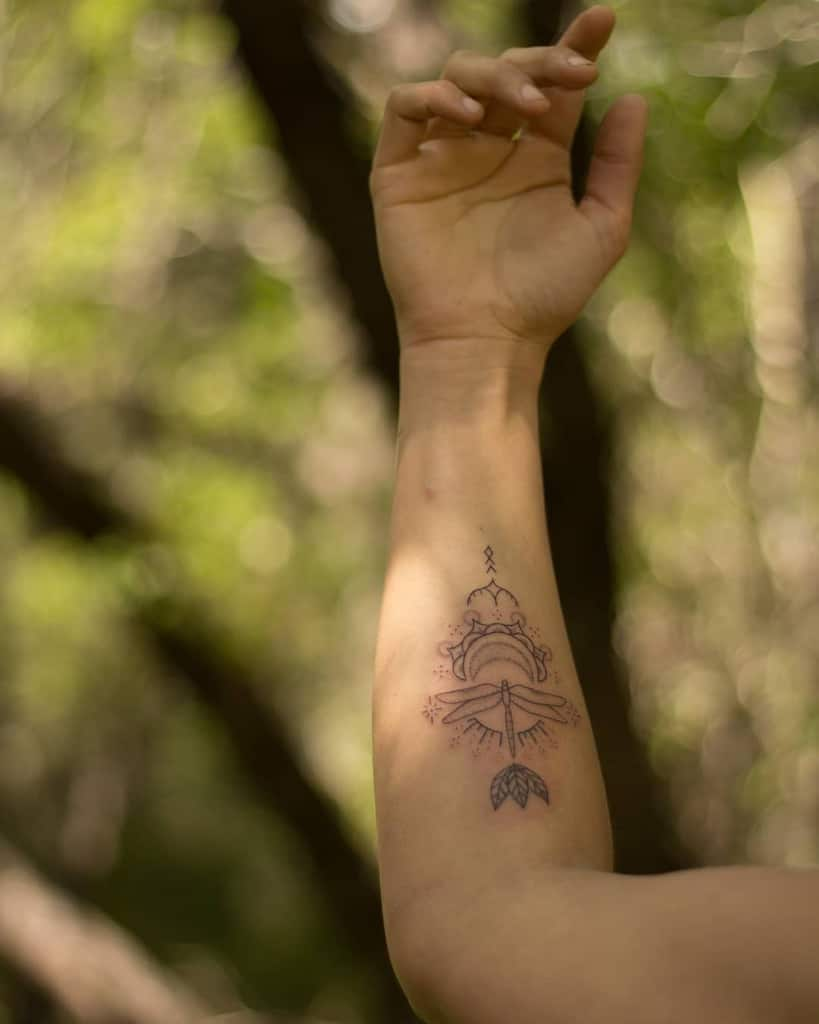 The intricate dragonfly inked around the sun fictions to pose the look of freedome and life