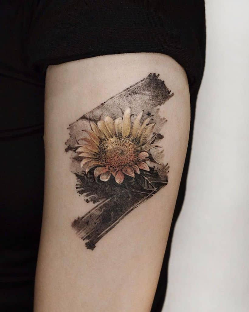 medium-sized muted color tattoo on upper arm of a realistic sunflower with a grey painted background