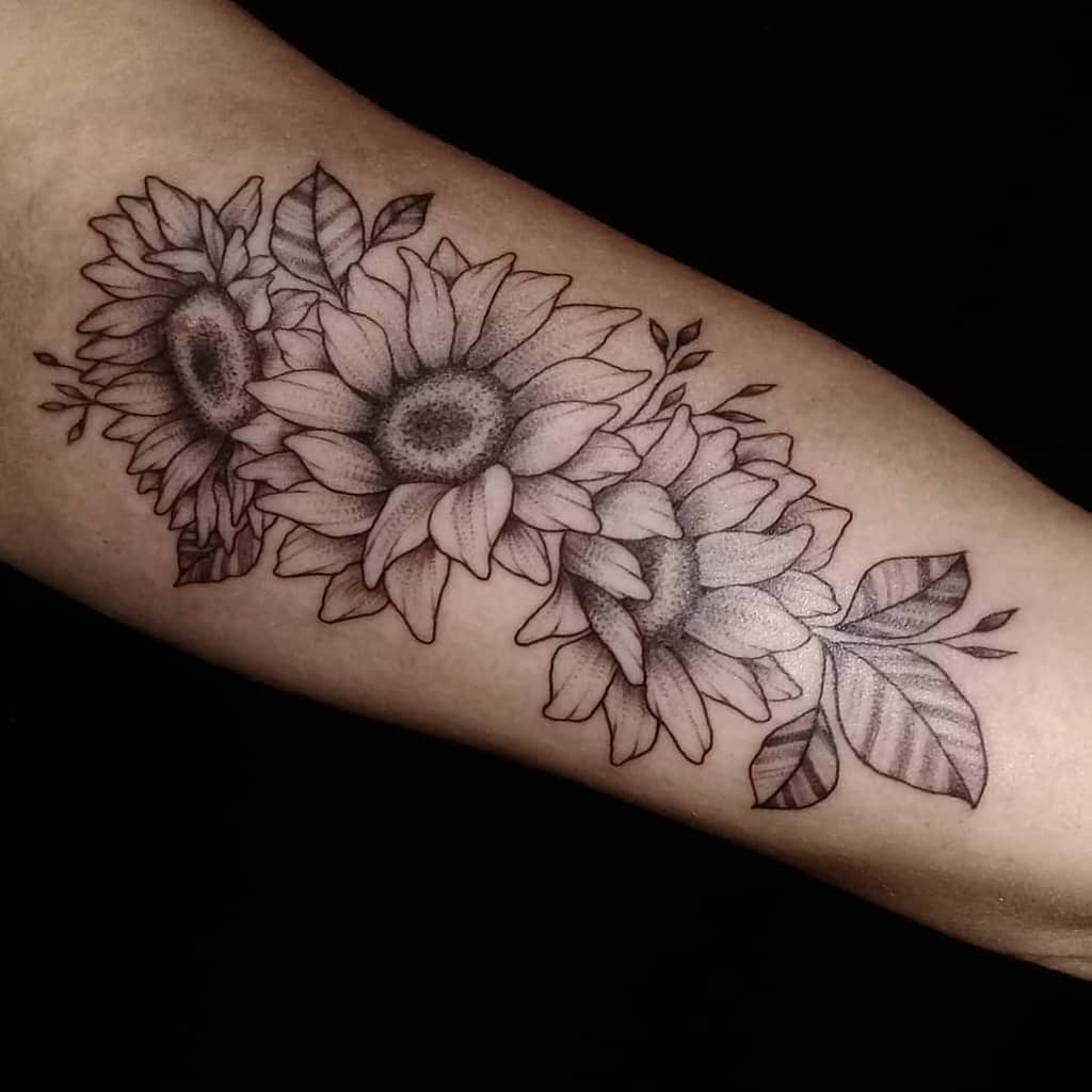medium-sized black and grey tattoo on forearm of a bouquet of three realistic sunflowers and leaves