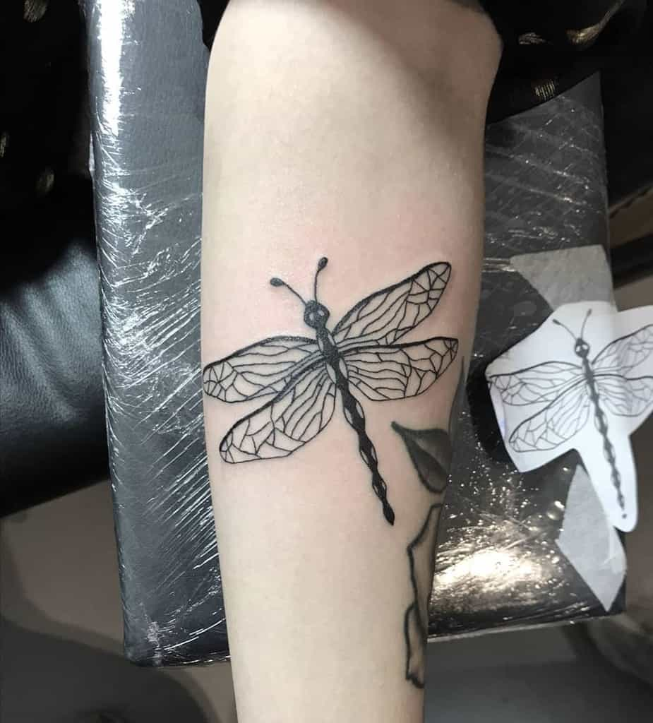 A tint of flower on the arm paired with the dragonfly to accentuate the image of tattoo'ing