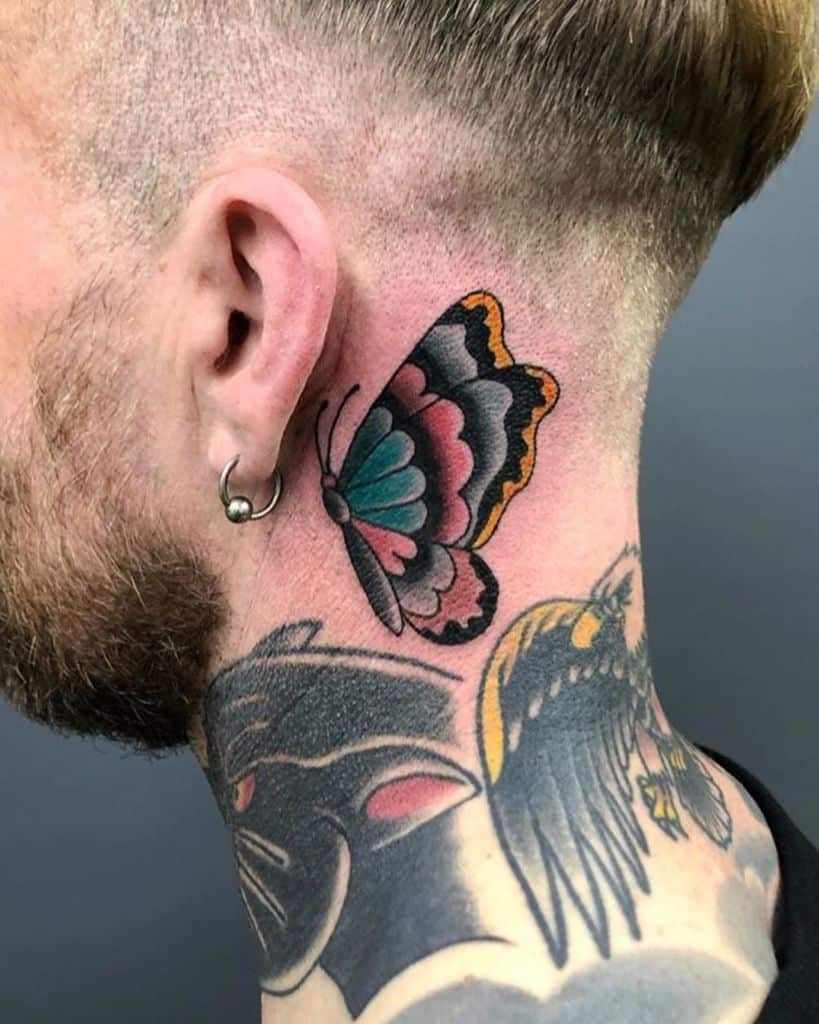 medium-sized traditional color tattoo behind man's ear of blue pink orange butterfly