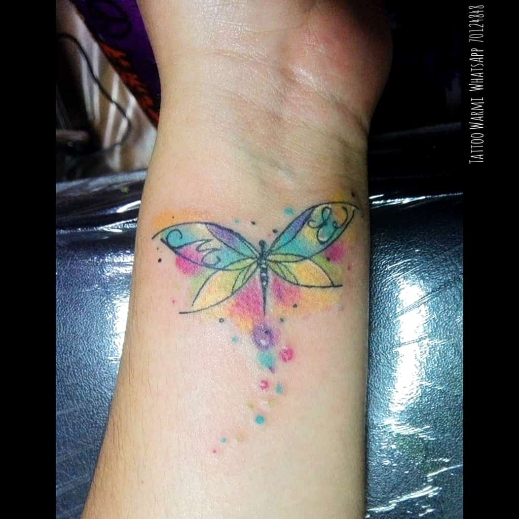 The inked dragonfly on the wrist with all it colorful glory showing the accents of life