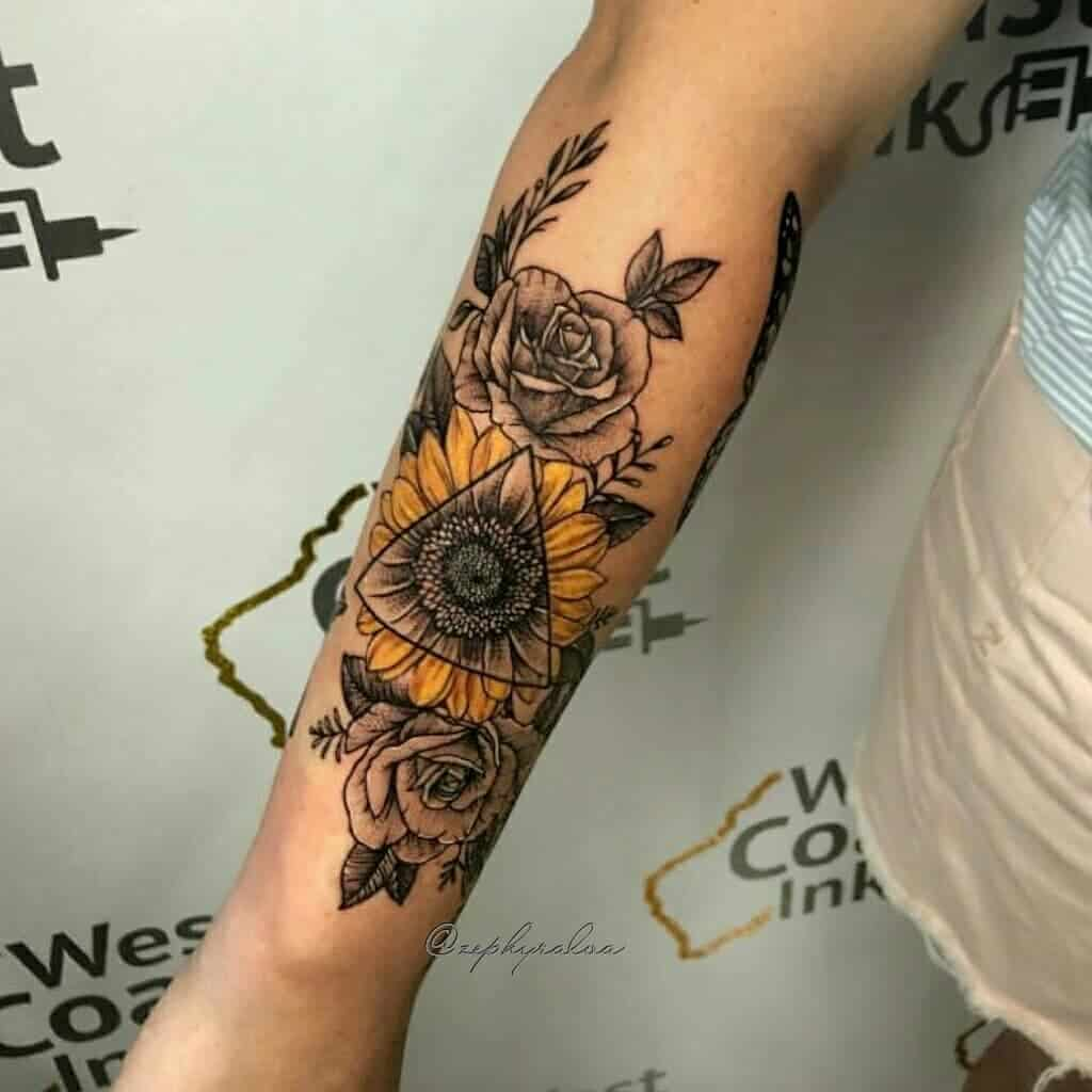 large color and black and grey tattoo on woman's forearm of a bouquet of a sunflower and roses with a triangle