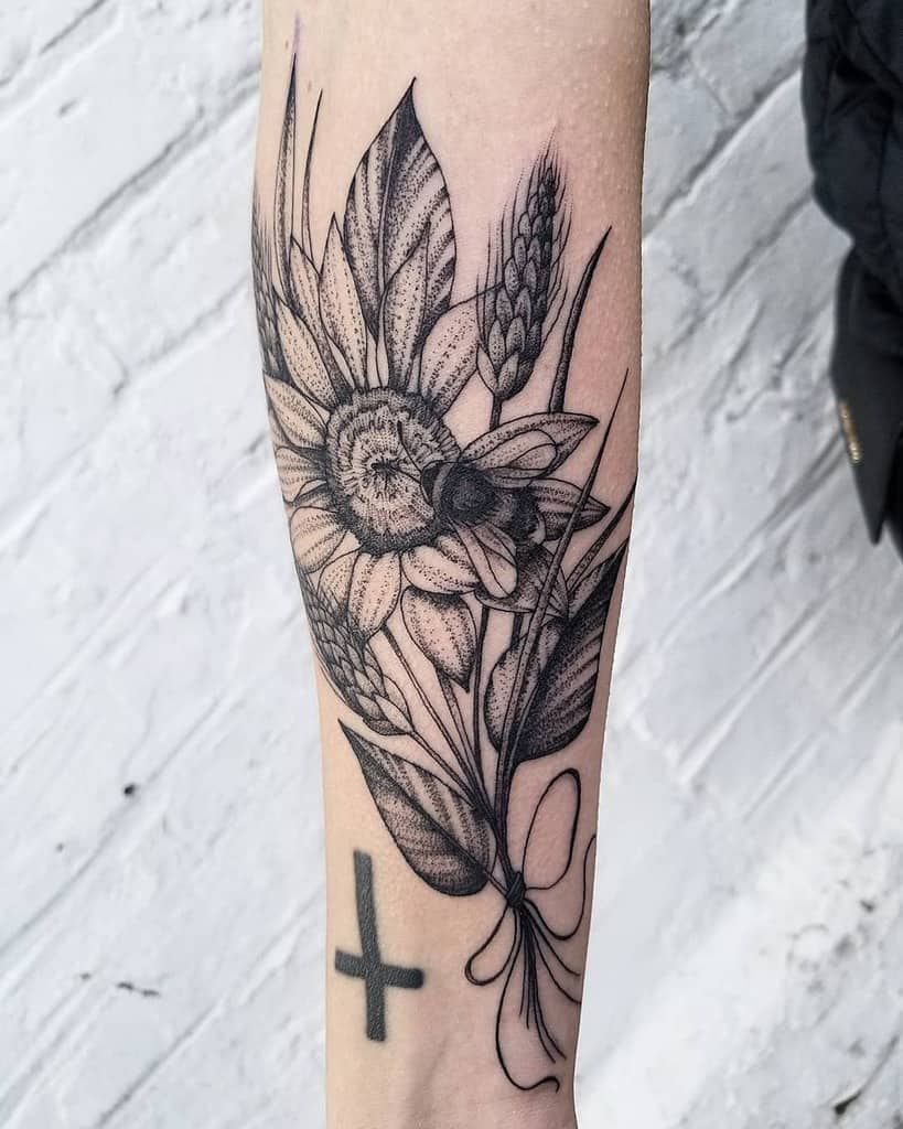 large black and grey tattoo on inner forearm of realistic bouquet of a sunflower and wheatgrass with a bumble bee