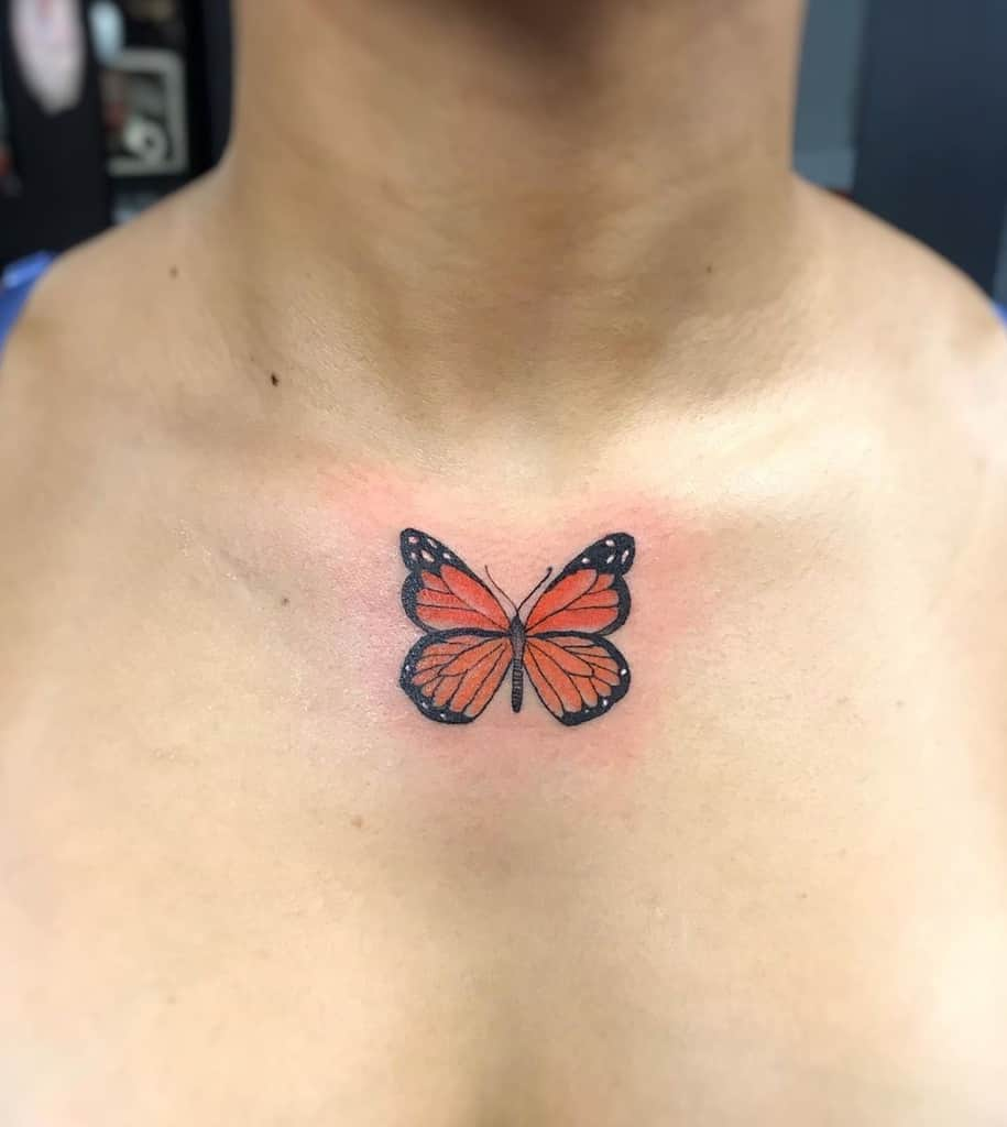 small color tattoo on woman's chest of a realistic orange tiger butterfly