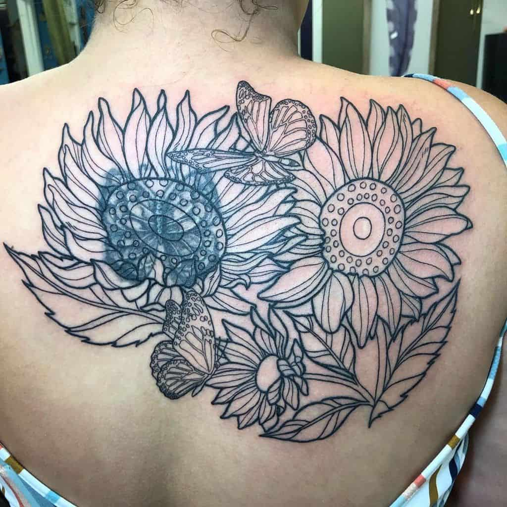 large cover-up black and grey tattoo on woman's upper back of bouquet of sunflowers with butterfly