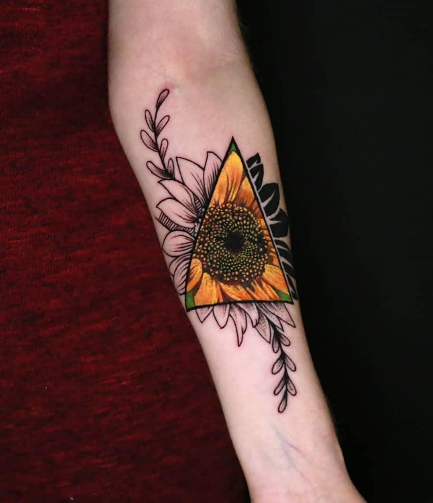 medium-sized color and black and grey surrealism tattoo on woman's forearm of a sunflower with a triangle