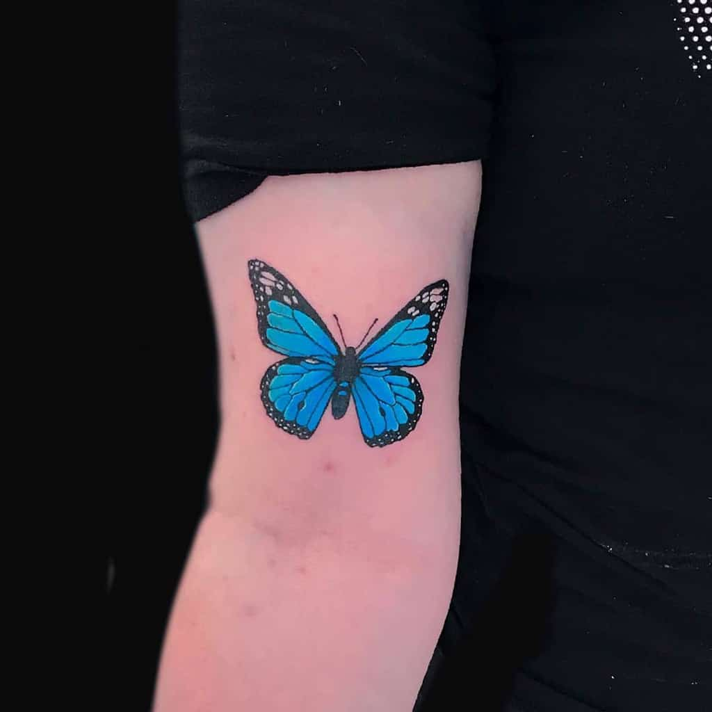 medium-sized color tattoo on woman's upper arm of a realistic blue monarch butterfly