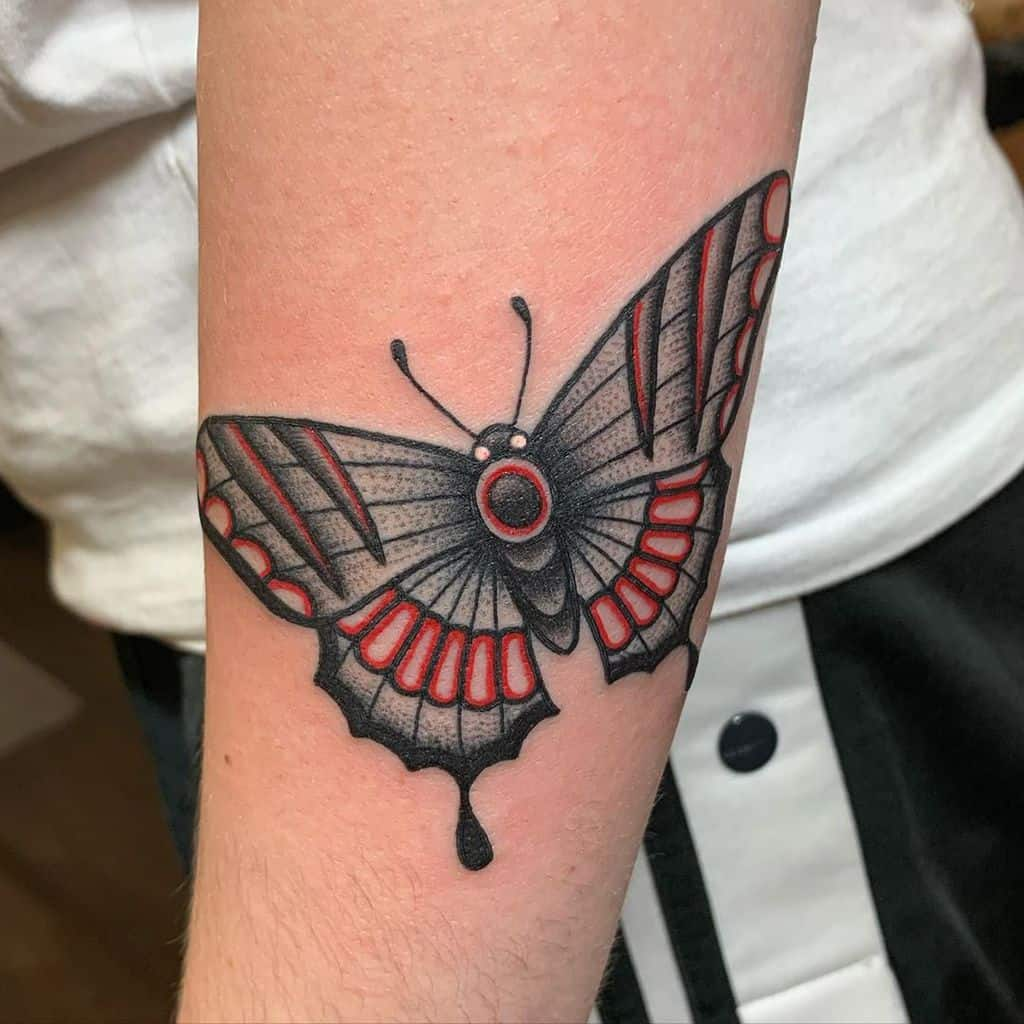 medium-sized color tattoo on woman's lower leg of black and red traditional butterfly