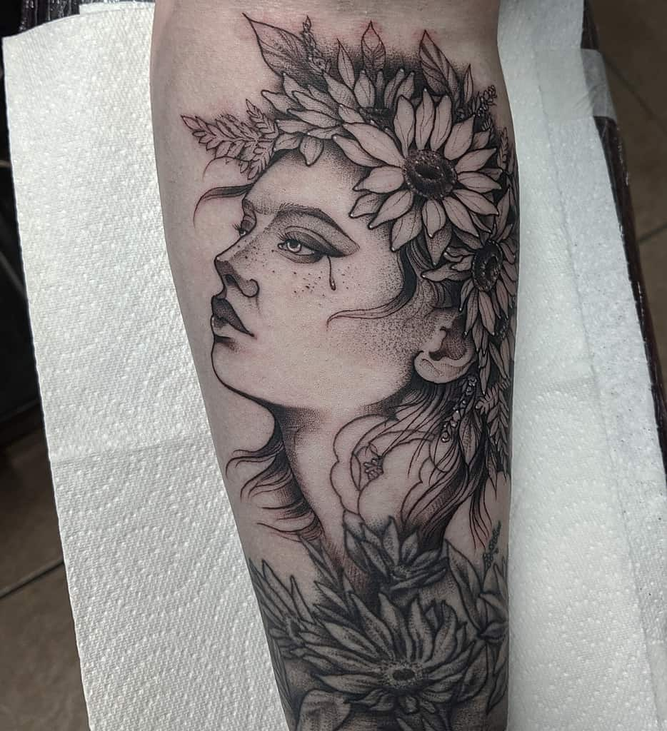 large black and grey tattoo on lower leg of sad woman's face with sunflower and flowers in her hair like a crown