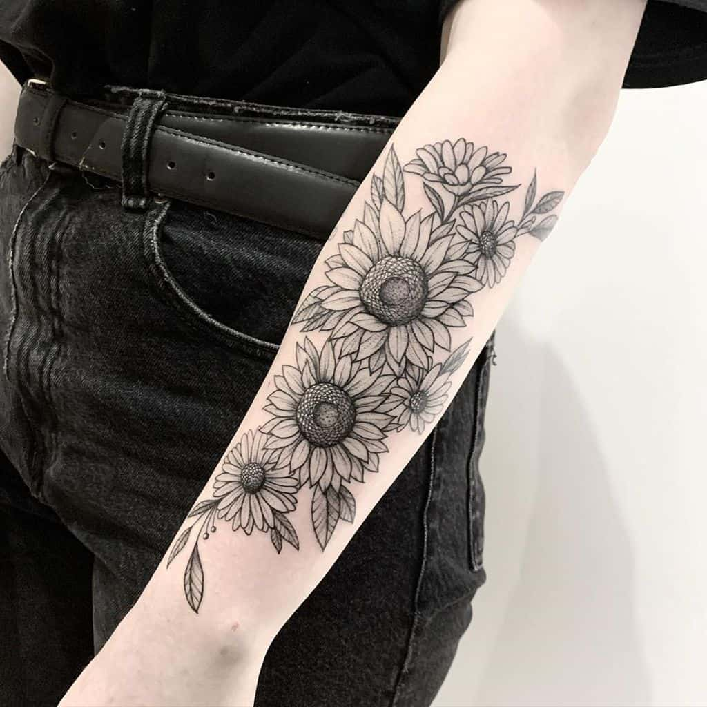 large black and grey realistic sunflower and daisy bouquet tattoo on woman's forearm