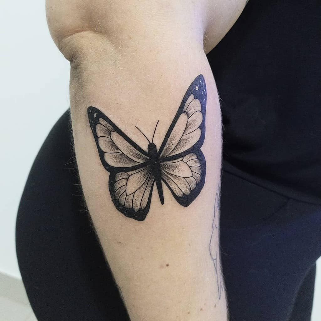 large bold black and grey tattoo on woman's forearm of realistic butterfly