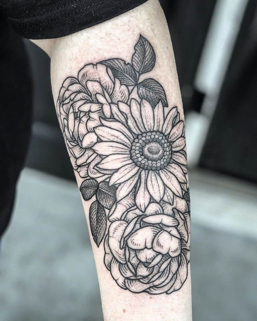 large black and grey line tattoo on man's forearm of a bouquet of a sunflower and two roses behind it