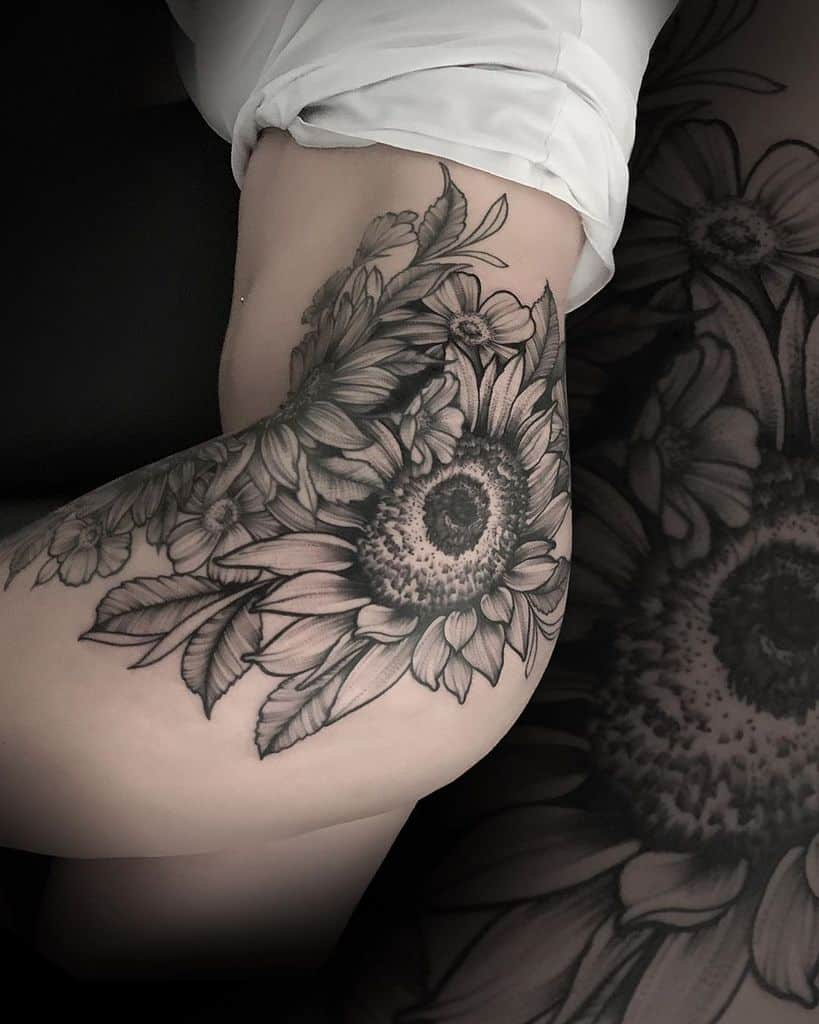 large black and grey realistic tattoo on woman's hip of a bouquet of sunflowers and pansies