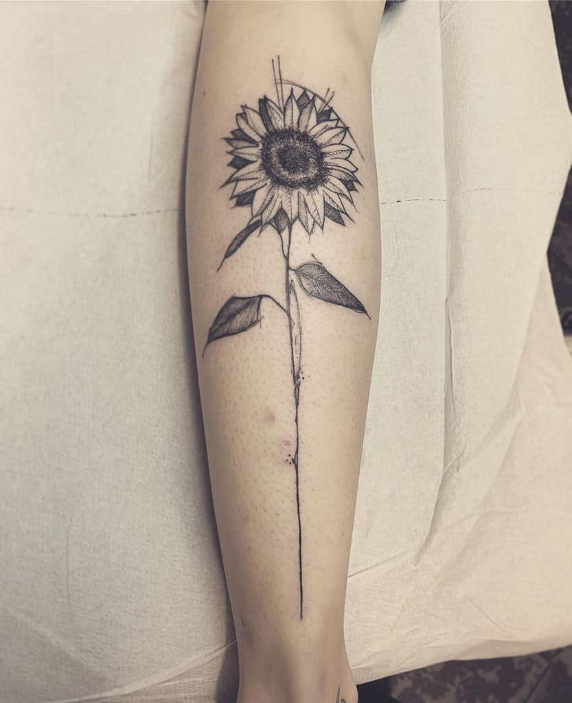 large black and grey surrealism tattoo on woman's lower leg of a sunflower with stem
