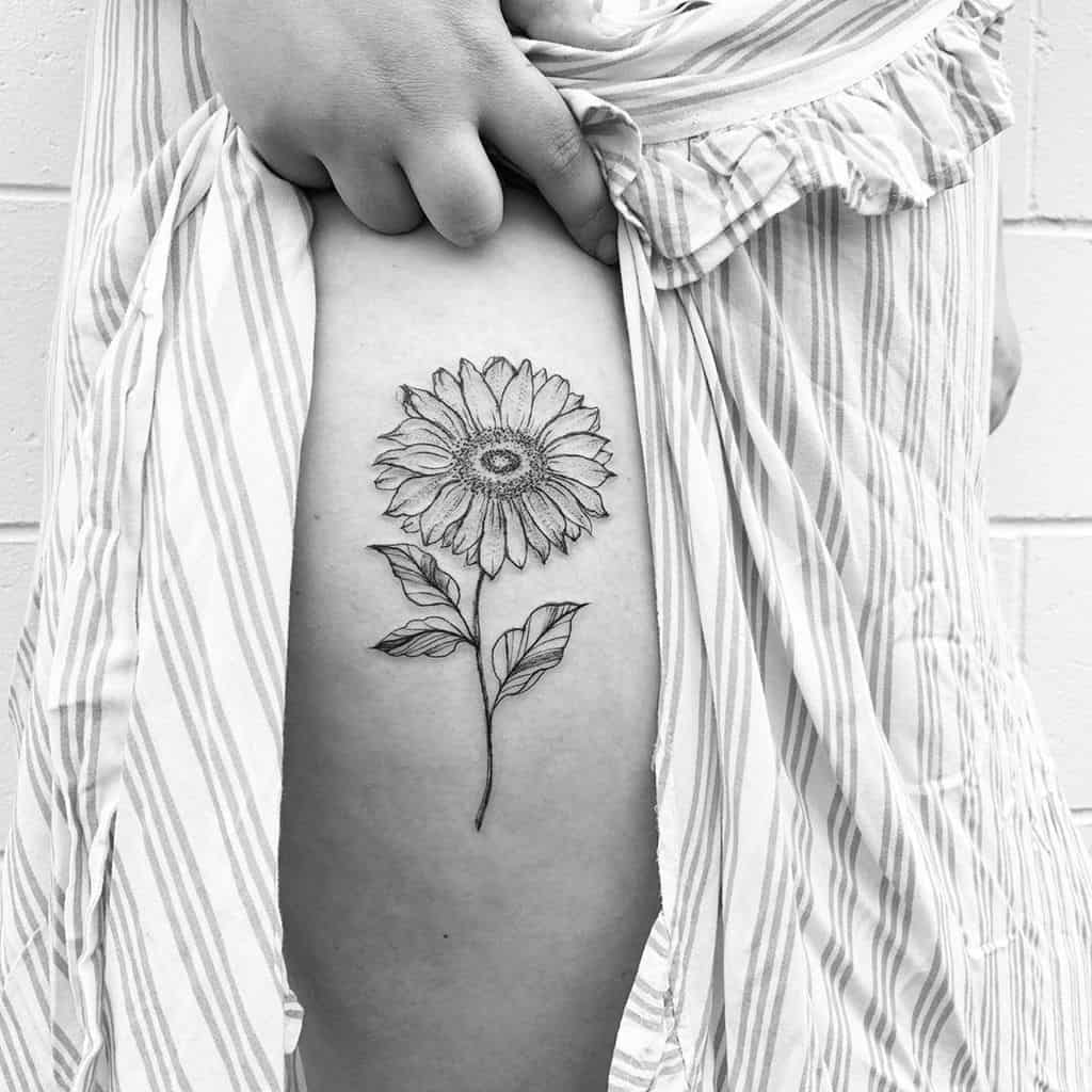 medium-sized black and grey tattoo on woman's thigh of a realistic sunflower with stem