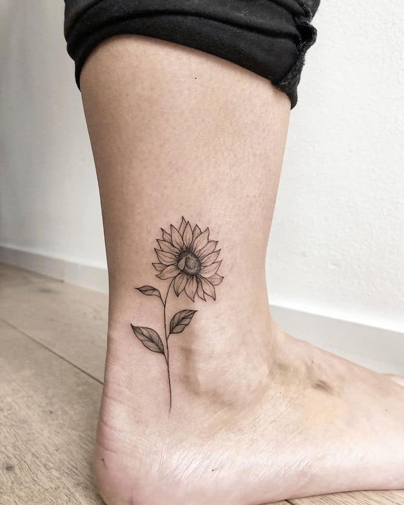 realistic black and grey tattoo on a woman's ankle of a dainty sunflower