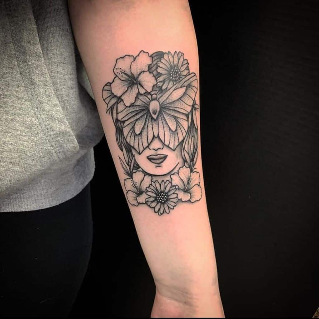 large black and grey tattoo on woman's forearm of woman's face with butterfly over eyes and flowers around it