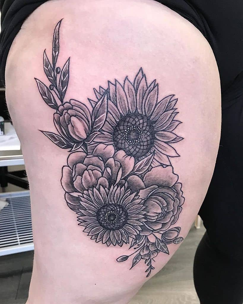large black and grey tattoo on woman's thigh of a bouquet of sunflowers and peonies