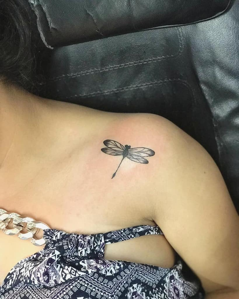 The miniature tattoo shaping into a dragonfly signifying the elegance and femininity at the shoulder
