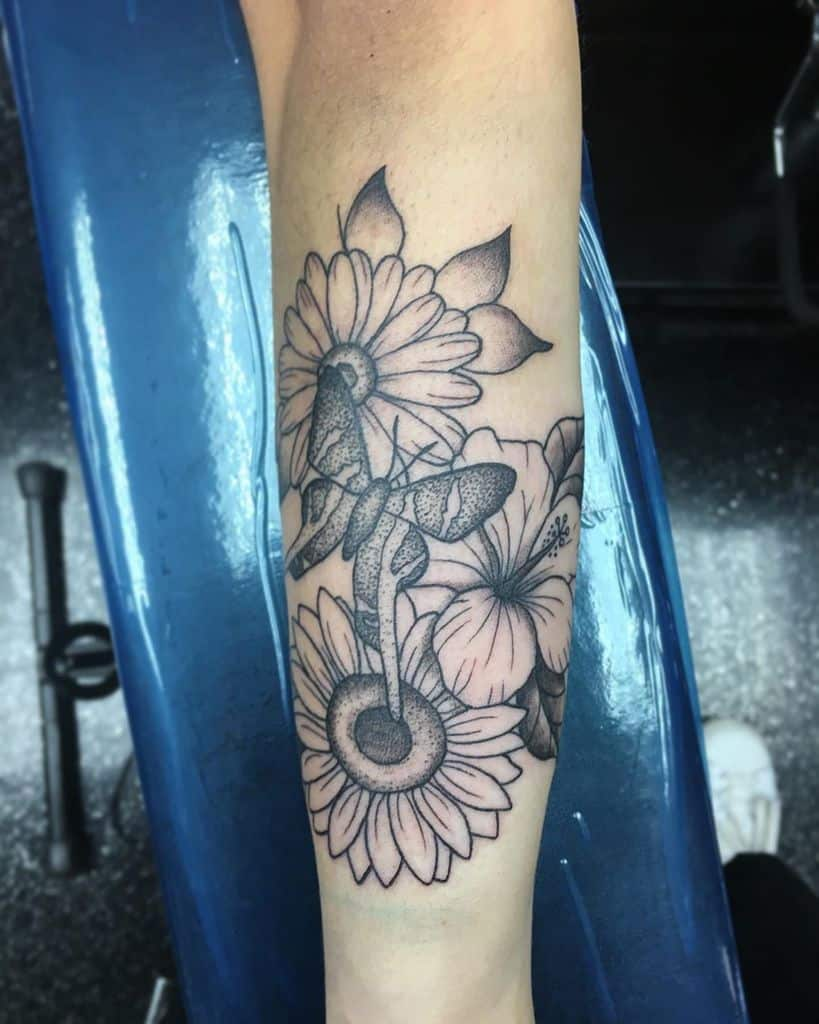 large black and grey tattoo on lower leg of a bouquet of sunflower, daisy, and hibiscus with butterfly