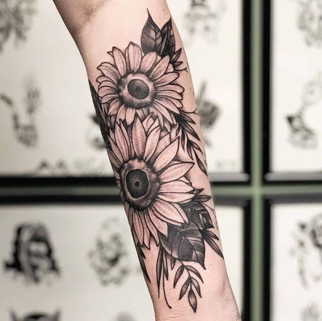large black and grey realistic tattoo on woman's forearm of a bouquet of sunflowers