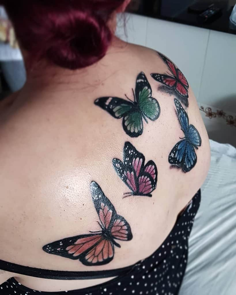 large color tattoos on a woman's upper back of multiple realistic butterflies