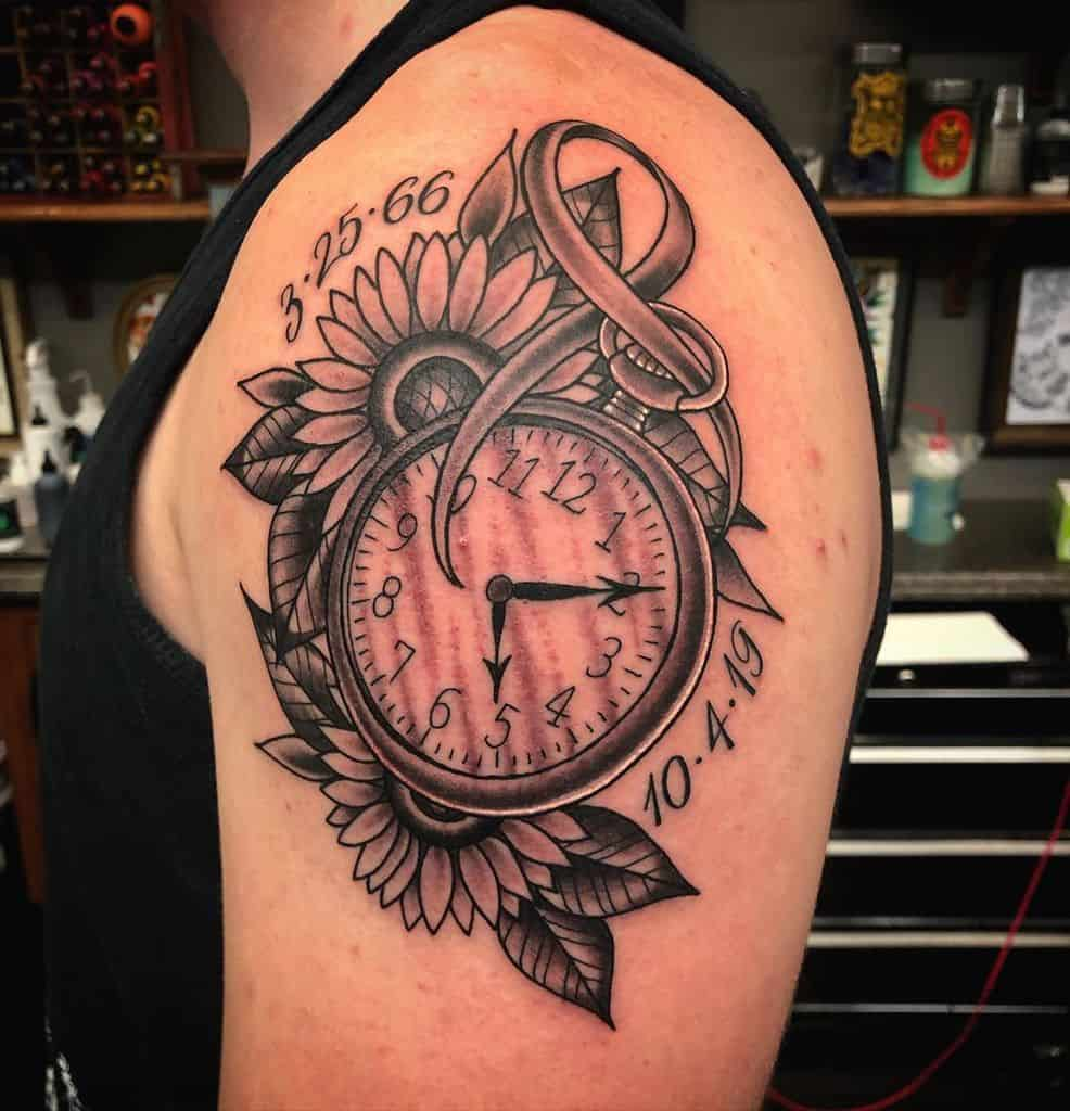 large black and grey traditional tattoo on man's upper arm of a pocket watch with two sunflowers and leaves behind