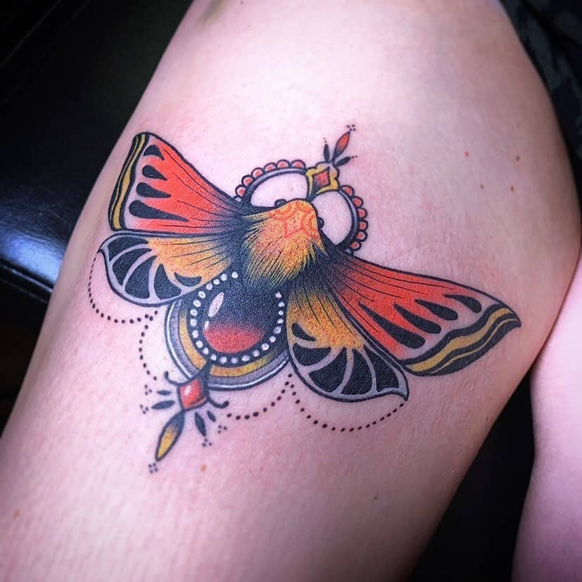 medium-sized traditional color tattoo on woman's lower leg of orange and yellow ornamentalbutterfly