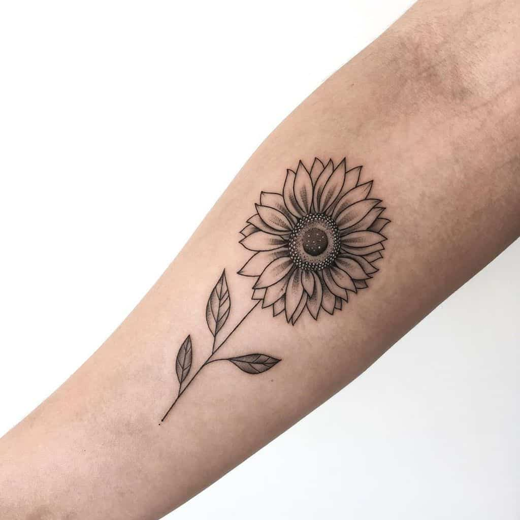 traditional black and grey sunflower tattoo on woman's forearm