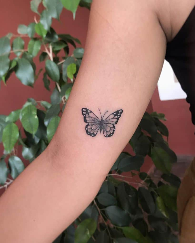 small black and grey tattoo on woman's upper arm of realistic butterfly