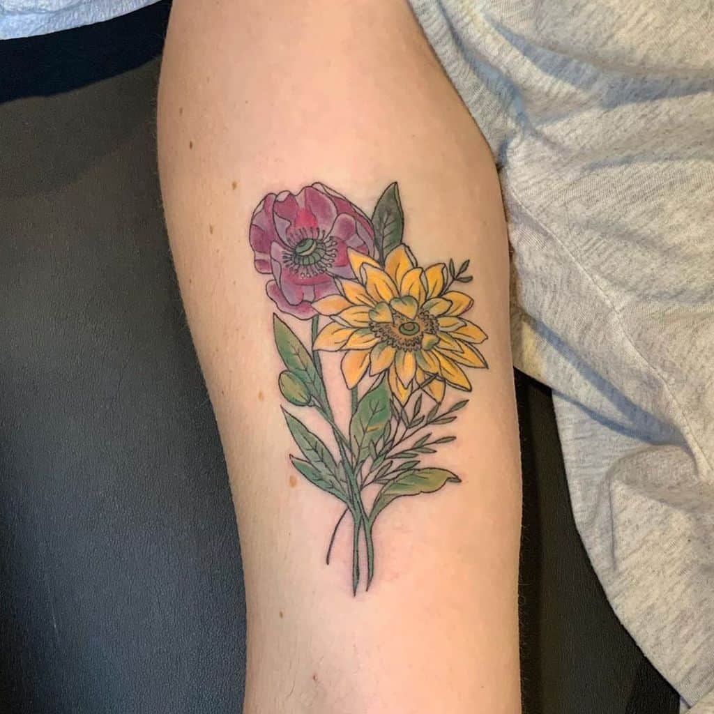 large color tattoo on woman's upper arm of a small bouquet of a sunflower and a poppy