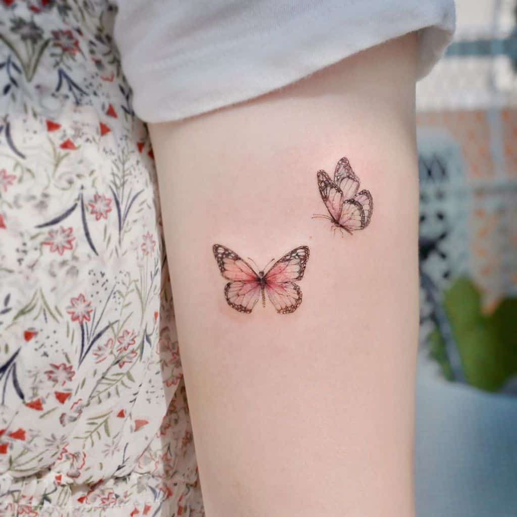 small color tattoo on woman's upper arm of two delicate pink butterflies