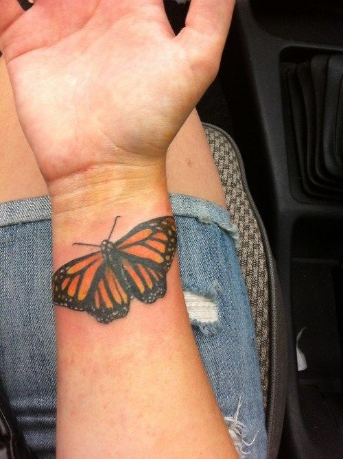 medium-sizec color tattoo on man's wrist forearm of realistic orange tiger butterfly