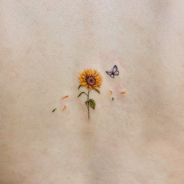 small color tattoo on woman's spine of a realistic sunflower shedding petals with stem and butterfly